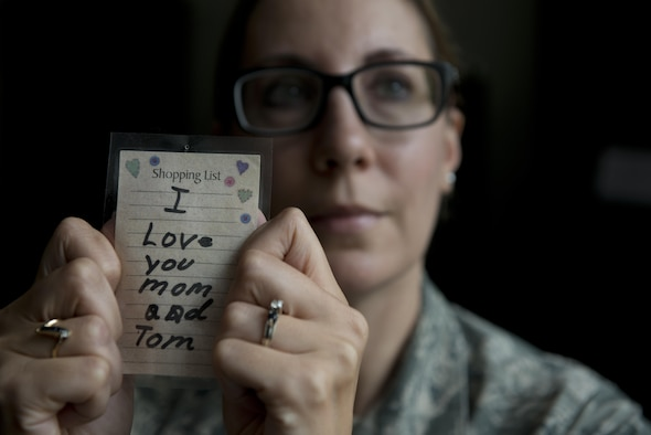 Senior Master Sgt. Janet Lemmons, the 176th Force Support Squadron sustainment and services superintendent, holds up a note her son Tommy wrote to her and his stepfather, Tom, when he was younger. She found the note among a pile of old receipts when she was looking to trade in some diamond earrings after his death. Lemmons tells everyone the note is a thousand times better than diamonds and she keeps it at her desk. (U.S. Air Force photo/Senior Airman Kyle Johnson)