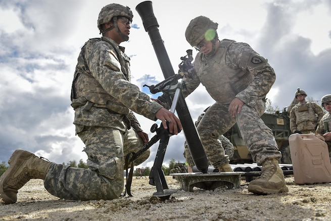 Army Pfc. Camill Hernandez, left, and Spc. Caleb Clark prepare to fire an 81mm mortar during Arctic Anvil 2016 at the Yukon Training Area near Fort Wainwright, Alaska, July 23, 2016. The multinational exercise aims to improve interoperability. Air Force photo by Justin Connaher