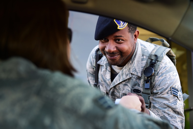Senior Airman Stone Robinson, 460th Space Wing Security Forces Squadron gate guard, checks entry qualifications of a fellow service member July 20, 2016, at Buckley Air Force Base, Colo. The job of upholding the safety and security of military installations and its members rests on the shoulders of defenders and one way they do so is by checking the credentials of those who enter the installation. (U.S. Air Force photo by Airman 1st Class Gabrielle Spradling/Released)