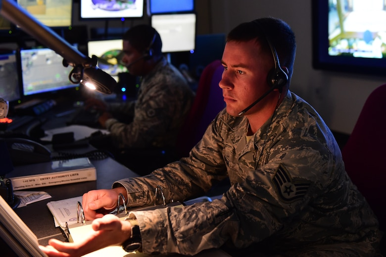 Staff Sgt. Tyler Bush, Base Defense Operations Center controller, and Staff Sgt. Alexander Parrilla, BDOC controller, review procedures July 20, 2016, at Buckley Air Force Base, Colo. BDOC maintains positive security of the base, controls the dispatch and alarm systems and entry control procedures while also providing emergency services to Buckley and local authorities. (U.S. Air Force photo by Airman 1st Class Gabrielle Spradling/Released)