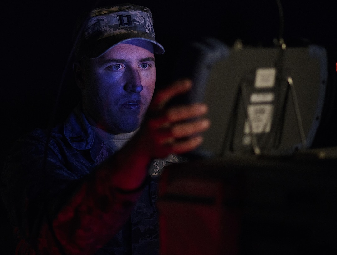 """Using minimum light so he can't be seen by exercise Red Flag players, Capt. Brian Goodman, 527th Space Aggressors, fine-tunes his equipment before attempting to degrade a fighter squadron's space capabilities, July 21, 2016 at Nellis Air Force Base, Nevada. """"There are adversaries who see how much space brings to the table and how much space has become critical to us in waging and winning wars. They want to take that piece away,"""" said Goodman. (U.S. Air Force photo/Tech. Sgt. David Salanitri)"""