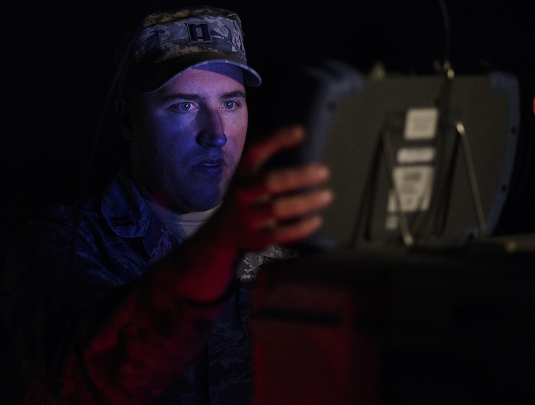 "Using minimum light so he can't be seen by exercise Red Flag players, Capt. Brian Goodman, 527th Space Aggressors, fine-tunes his equipment before attempting to degrade a fighter squadron's space capabilities, July 21, 2016 at Nellis Air Force Base, Nevada. ""There are adversaries who see how much space brings to the table and how much space has become critical to us in waging and winning wars. They want to take that piece away,"" said Goodman. (U.S. Air Force photo/Tech. Sgt. David Salanitri)"