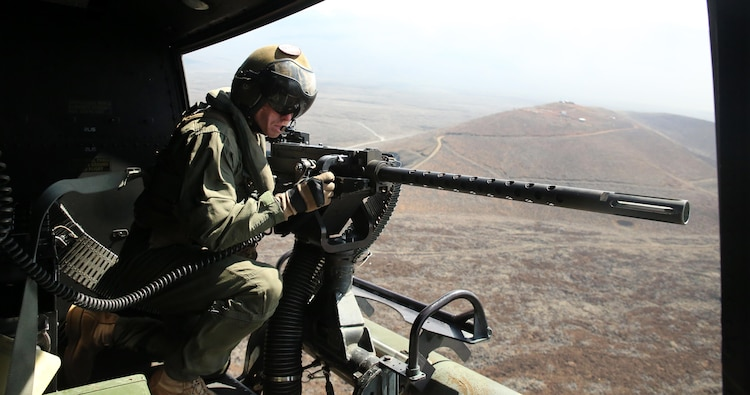 Cpl. Christopher Neumann aims his GAU-21 .50 caliber machine gun during a close air support exercise at Pohakuloa Training Area, Hawaii, July 19, 2016. Neumann is participating in Rim of the Pacific 2016, a multinational military exercise, from June 29 to Aug. 8 in and around the Hawaiian Islands. RIMPAC offers the U.S. military the opportunity to train with partners and allies in the Pacific region. Neumann, a native of Wells, Maine, is a UH-1Y Huey crew chief with Marine Light Attack Helicopter 367, which supports III Marine Expeditionary Force. (U.S. Marine Corps Photo by Cpl. Natalie A. Dillon)