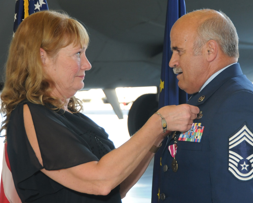 Retired Master Sgt. Lori Dixon pins the retirement pin on her husband Chief Master Sgt. Bill Dixon, former aircraft maintenance superintendent with the 168th Aircraft Maintenance Squadron, Alaska Air National Guard, during his retirement ceremony here at Eielson AFB, Alaska June 29, 2016. Dixon retired from military service after a 41-year career that spanned almost five decades, completing the last 20 years at this interior-Alaska installation. (U.S. Air National Guard photo by Senior Master Sgt. Paul Mann/Released)