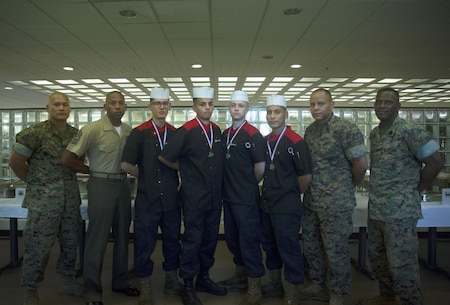 Competitors in the Futenma Mess Hall Chef of the Month competition pose for photos with the senior enlisted judges after receiving awards for their performance July 22 on Marine Corps Air Station Futenma, Okinawa, Japan. The monthly competition is an opportunity for the Marines who are performing well in the workplace and seeking opportunities to better themselves through merit boards and other events. During the competition, the contestants must plan a full multi-course meal, cook the dishes and serve it to a panel of judges who evaluate their meal based on taste, appearance, originality and the Marines' oral presentations explaining each course.