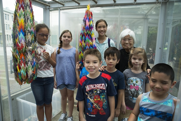 Kikuko Shinjo, better known as 'Shinjo-Sensei,' an 89 year-old native of Iwakuni and survivor of the atomic bombing in Hiroshima during World War II, poses with children from Marine Corps Air Station Iwakuni at the Children's Peace Monument at Hiroshima Peace Memorial Park, Japan, July 15, 2016. Shinjo invited a group of MCAS Iwakuni residents to help her donate 1,000 paper cranes, which she folded, to the Children's Peace Monument at Hiroshima Peace Memorial Park as a symbol for peace. (U.S. Marine Corps photo by Lance Cpl. Donato Maffin)
