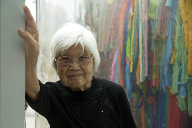 Kikuko Shinjo, better known as 'Shinjo-Sensei,' an 89 year-old native of Iwakuni and survivor of the atomic bombing in Hiroshima during World War II, poses in front of paper cranes donated to the Children's Peace Monument at the Hiroshima Peace Memorial Park, Japan, July 15, 2016. Shinjo invited a group of Marine Corps Air Station Iwakuni residents to help her donate 1,000 paper cranes, which she folded, to the Children's Peace Monument at Hiroshima Peace Memorial Park as a symbol for peace. (U.S. Marine Corps photo by Lance Cpl. Donato Maffin)