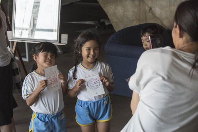 Students of Iwakuni-Kawashimo Kindergarten pose with zero hangar stamps they received during a school visit at Marine Corps Air Station Iwakuni, Japan, July 21, 2016. The school visit is a time honored tradition between the base and the local community and holds a lasting memory with the visiting students. (U.S. Marine Corps photo by Cpl. Nathan Wicks)