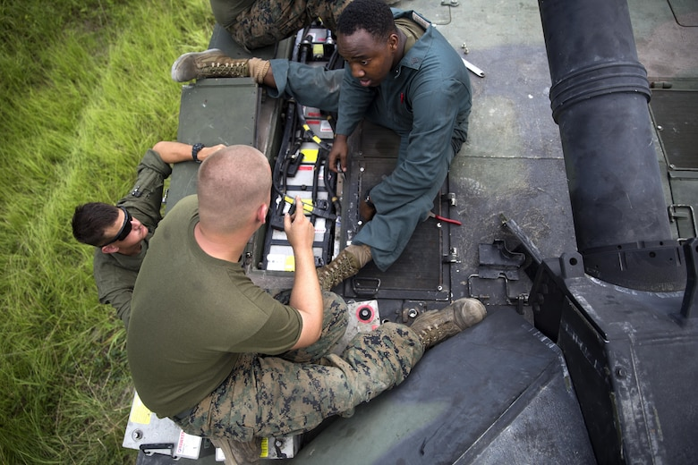 Sgt. Mark tucker and Cpl. Charles Vollmer of Fox Company, 4th Tank Battalion, work to fix the batteries in the M1A1 Abrams battle tank they sit on during a training exercise July 19, 2016. The exercise brought the reserve Marines together with elements of 2nd Tank Bn. to train in the event they deploy as one battalion in the future. (U.S. Marine Corps photo by Sgt. Matthew Callahan)