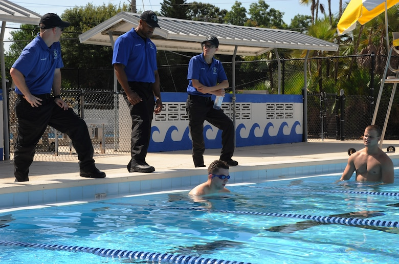 Members of the 6th Security Forces Squadron marine patrol brief two Airmen about the requirements of marine patrol tryouts at Bobby Hicks Pool in Tampa, Fla., July 21, 2016. To qualify to be a marine patrolman, Airmen must be able to complete a 200-meter freestyle swim, a 25-meter underwater swim, and tread water for five minutes while wearing the Airman battle uniform. (U.S. Air Force photo by Airman Adam R. Shanks)