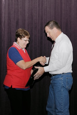 "Retiring DLA Disposition Services employee Wendy Kropp surprises activity director Mike Cannon with the ""Beautiful Battle Creek Award"" July 22."