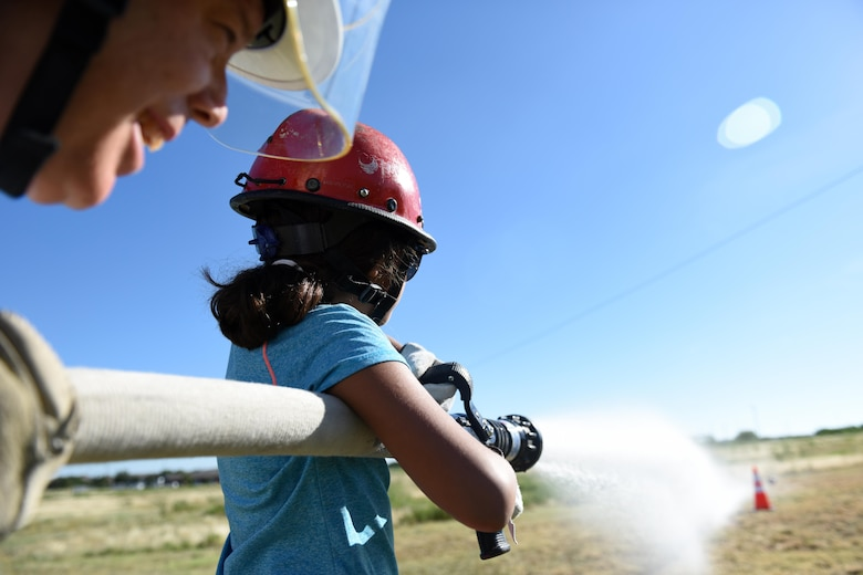 A young girl and Jeff T. Wilkins, Goodfellow Fire Department Chief, spray a target with a fire hose during the Junior Firefighter Camp at the Goodfellow Fire Department, July 20, 2016. Each participant learned how to carry and control a firehose by shooting a soccer ball off a cone. (U.S. Air Force photo by Airman 1st Class Caelynn Ferguson/Released)