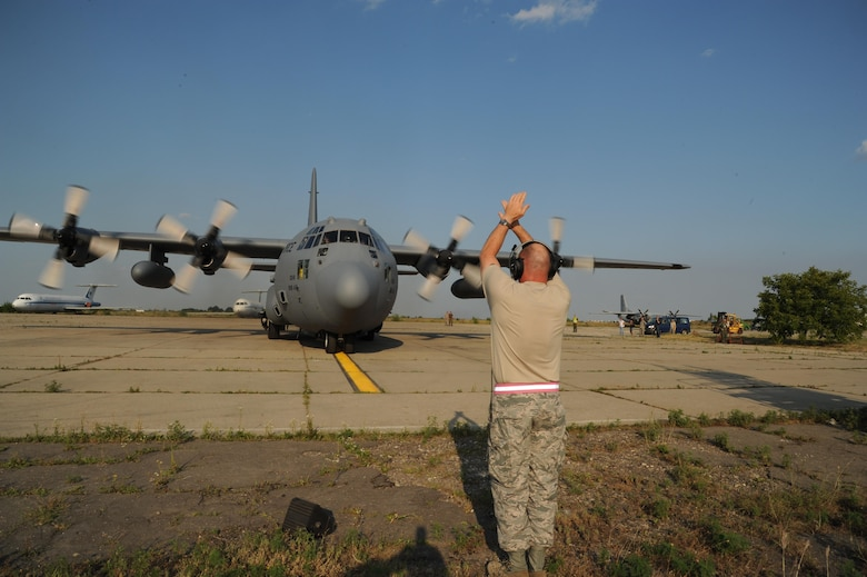 Chief Master Sgt. Leon Alexander directs the aircraft to stop in its parking place on arrival at Otopeni Air Base, Romania.  Otopeni is located on the outskirts of Bucharest.