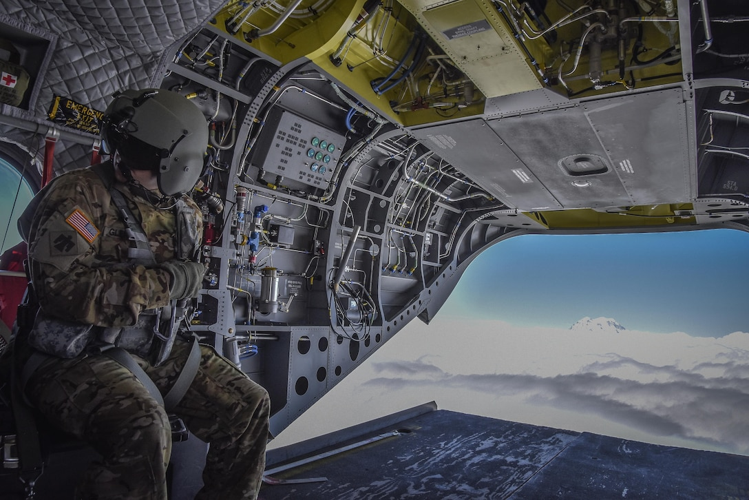 U.S. Army Reserve Sgt. Dan Glenn, 1-214th General Support Aviation Battalion, Bravo Company, communicates with fellow aircrew members during a flyover near Mount Rainier, Wash., onboard a CH-47 Chinook, July 22, 2016.  The 1-214th GSAB, has a unique mission which involves working with the Washington National Park  and provides support for search and rescue missions as well as fire rescue missions in the area.  (U.S. Army photo by Master Sgt. Marisol Walker/Released)