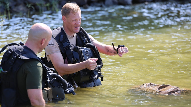 Master Sgt. Brad Colbert, project officer for small craft and special projects with Reconnaissance and Amphibious Raids at Marine Corps Systems Command, describes the dive course to a Marine diver July 18 at Lake Anna in Spotsylvania, Virginia. Colbert and other members of the RAR team worked with several local Marine combatant divers to conduct tests of potential upgrades to the Diver Propulsion Device to improve its speed and controllability.