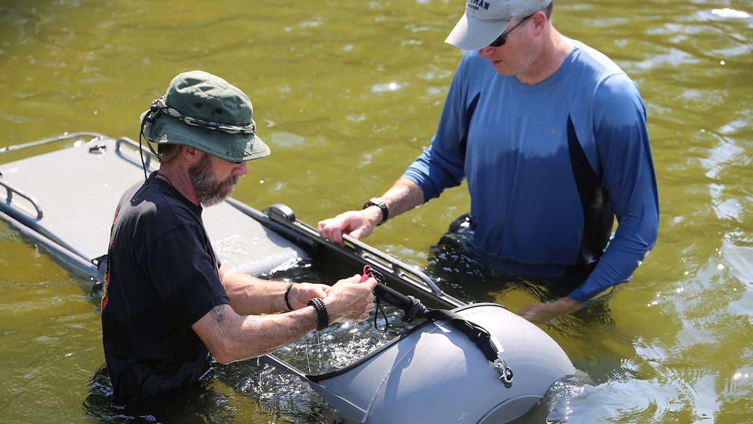 Ed Maziarski (left) and Jake Feeney of Reconnaissance and Amphibious Raids at Marine Corps Systems Command prepare a diver propulsion device for testing July 18 at Lake Anna in Spotsylvania, Virginia. The team worked with Marine combatant divers to conduct tests of potential upgrades to the DPD to improve its speed and controllability.