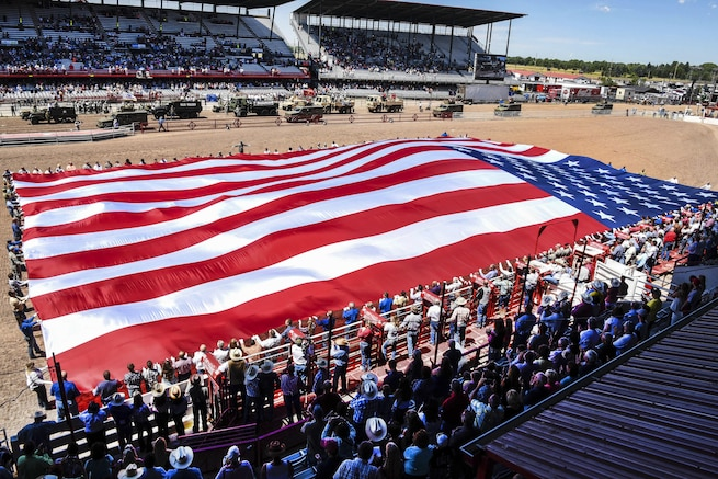 Service members and community volunteers unravel the American flag at Frontier Park in Cheyenne, Wyo., July 25, 2016. More than 200 volunteers participated in this year's Military Monday event. Air Force photo by Airman 1st Class Breanna Carter