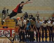 French referee Christophe Gomez and athletes from China, Germany and the U.S. -- along with two U.S. family members -- duck as a TNT Dunk Squad acrobat somersaults over their heads at end of the opening ceremony for the World Military Women's Basketball Championship at Marine Corps Base Camp Pendleton, Calif., July 25, 2016. Courtesy photo