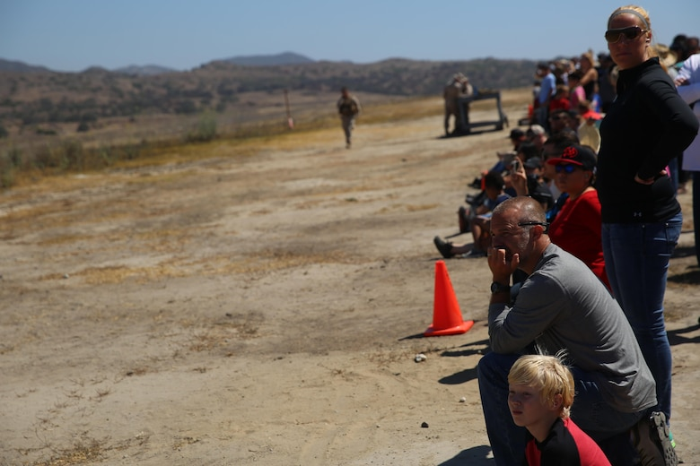 Marines and their family members position themselves behind cones during the helicopter gun run during a Jane Wayne Day event on Camp Pendleton, Calif., July 16, 2016. Pilots with Marine Light Attack Helicopter Training Squadron 303 shot rockets and ammunition at various targets from one UH-1Y Huey helicopter, two AH-1W Cobra helicopters and one AH-1Z Cobra helicopter. (U.S. Marine Corps photo by Lance Cpl. Shellie Hall)