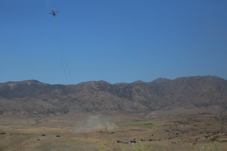 """An AH-1Z Viper helicopter sends rockets down range at targets during the """"helicopter gun run"""" during a Jane Wayne Day event on Camp Pendleton, Calif., July 16, 2016. Pilots with Marine Light Attack Helicopter Training Squadron 303 shot rockets and ammunition at various targets from one UH-1Y Huey helicopter, two AH-1W Cobra helicopters and one AH-1Z Cobra helicopter. (U.S. Marine Corps photo by Lance Cpl. Shellie Hall)"""