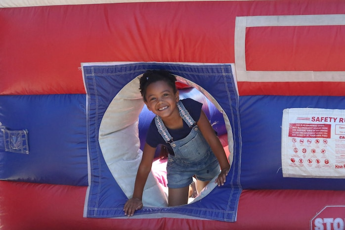 A girl plays in a bounce house during a Jane Wayne Day event on Camp Pendleton, Calif., July 16, 2016. The event included multiple live fire exercises, static displays of vehicles and helicopters, and a barbecue. (U.S. Marine Corps photo by Lance Cpl. Shellie Hall)