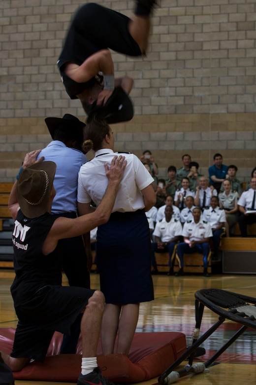A member of the Dunk Squad preforms an acrobatic flip over two international military athletes during the opening ceremony for the 2016 Conseil International Du Sport Militaire (CISM) World Military Women's Basketball Championship tournament July 25 at Camp Pendleton, California. The base is hosting the CISM World Military Women's Basketball Championship July 25 through July 29 to promote peace activities and solidarity among military athletes through sports. (U.S. Marine Corps photo by Sgt. Abbey Perria)