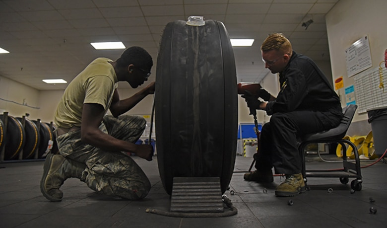 Airman 1st D'Andre Davis, 92nd Maintenance Squadron aerospace repair apprentice, assists in break down of a tire with Airman 1st Class Cody Mathews, 92nd MXS aerospace repair journeyman, at Fairchild Air Force Base July 22, 2016. The aerospace repair shop is tasked with wheel and tire assembly for all KC-135 Stratotanker operations within Pacific Air Force as well as KC-135 operations at Fairchild. (U.S. Air Force photo/Airman 1st Class Mackenzie Richardson)