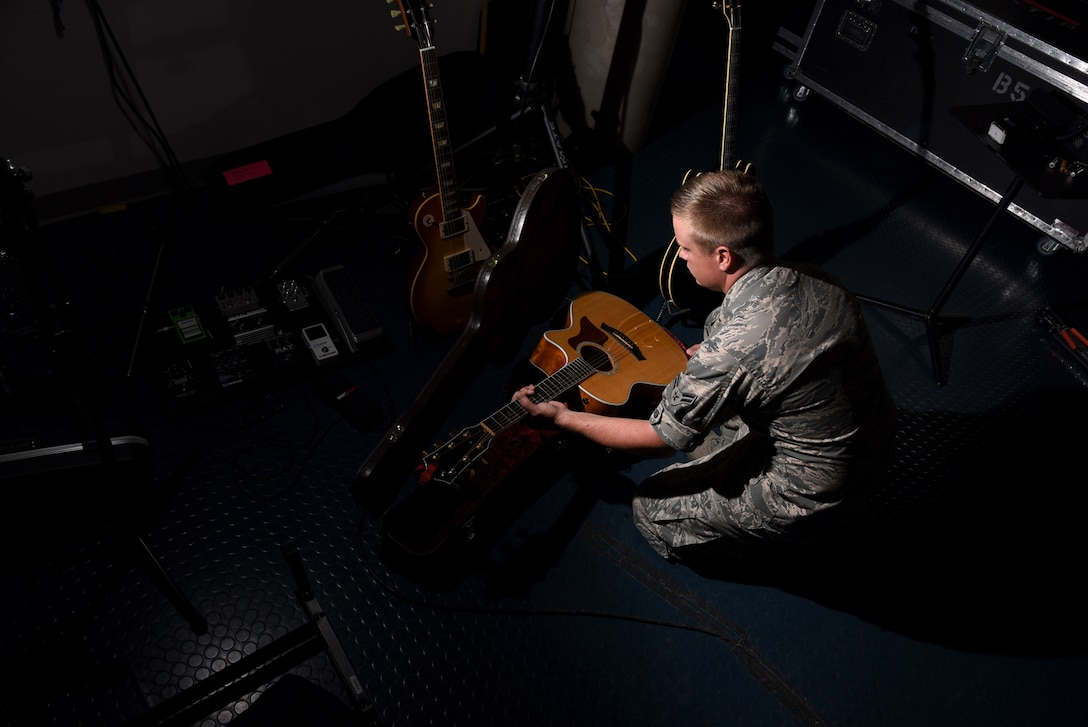 Airman 1st Class Jamie Teachenor, U.S. Air Force Academy Band and Wild Blue Country lead vocalist, removes his acoustic guitar from its case at Peterson Air Force Base, Colo., on July 20, 2016. Teachenor performs most of his songs while playing either the piano or the guitar. (U.S. Air Force photo by Airman 1st Class Dennis Hoffman)