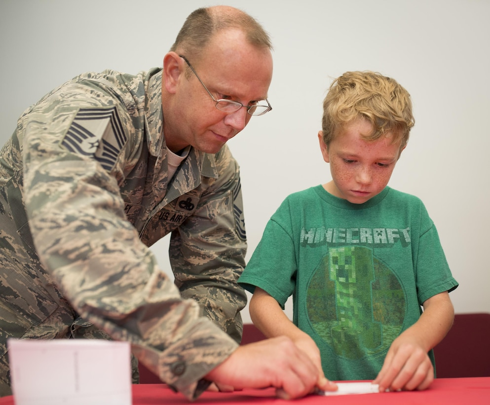 Chief Master Sgt. James Shelley, 33rd Maintenance Group, and his nine-year-old son, Jackson, fold a paper airplane together during a base reading program class July 26 at Eglin Air Force Base, Fla.  The class was taught by Ken Blackburn, Air Force Research Lab Munitions Directorate, who held the Guinness World Record for longest in-air paper airplane flight.  More than 30 kids and parents folded their planes based on Blackburn's instructions, then filled the base's digital library with tiny flying paper aircraft.  (U.S. Air Force photo/Samuel King Jr.)