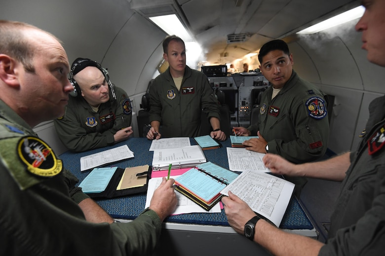Air battle managers assigned to the 970th Airborne Air Control Squadron discuss mission details on July 23, 2016, aboard an E-3 Sentry at Joint Base Pearl Harbor-Hickam, Hawaii, prior to a mission in support of Rim of the Pacific 2016. More than 125 Airmen from the 513th Air Control Group and 552nd Air Control Wing are deployed to Hawaii in support of the RIMPAC 2016 exercise. Twenty-six nations, more than 40 ships and submarines, more than 200 aircraft and 25,000 personnel are participating in RIMPAC from June 30 to Aug. 4, in and around the Hawaiian Islands and Southern California. The world's largest international maritime exercise, RIMPAC provides a unique training opportunity that helps participants foster and sustain the cooperative relationships that are critical to ensuring the safety of sea lanes and security on the world's oceans. RIMPAC 2016 is the 25th exercise in the series that began in 1971. (U.S. Air Force photo by 2nd Lt. Caleb Wanzer)