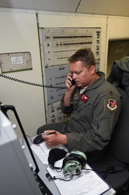 Maj. Shawn Kilbourne, a pilot assigned to the 513th Operations Support Squadron, talks on a satellite phone July 23, 2016, aboard an E-3 Sentry near the Hawaiian Islands during a mission in support of Rim of the Pacific 2016. More than 125 Airmen from the 513th Air Control Group and 552nd Air Control Wing are deployed to Hawaii in support of the RIMPAC 2016 exercise. Twenty-six nations, more than 40 ships and submarines, more than 200 aircraft and 25,000 personnel are participating in RIMPAC from June 30 to Aug. 4, in and around the Hawaiian Islands and Southern California. The world's largest international maritime exercise, RIMPAC provides a unique training opportunity that helps participants foster and sustain the cooperative relationships that are critical to ensuring the safety of sea lanes and security on the world's oceans. RIMPAC 2016 is the 25th exercise in the series that began in 1971. (U.S. Air Force photo by 2nd Lt. Caleb Wanzer)