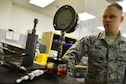 U.S. Air Force Staff Sgt. Zane Wilms precision measurement equipment laboratory technician, calibrates a jack pressure gauge behind a shield at Shaw Air Force Base, S.C., July 11, 2016. The jack pressure gauge is calibrated by PMEL Airmen to allow elevation of an aircraft without the use of its wheels. (U.S. Air Force photo by Airman 1st Class Christopher Maldonado)