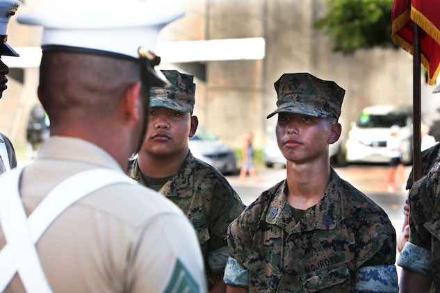 A JROTC Cadet receives instruction on close order drill from Sgt. Antonio Garay, a field radio operator and color sergeant with 3rd Marine Division during Guam's annual Liberation Day Parade July 21, 2016. The color guard marched in the parade for the first time since 3rd Marine Division liberated Guam 72 years ago. The legacy between past and present Marines and Sailors of 3rd Marine Division lives on through events such as the annual Liberation Day Parade.