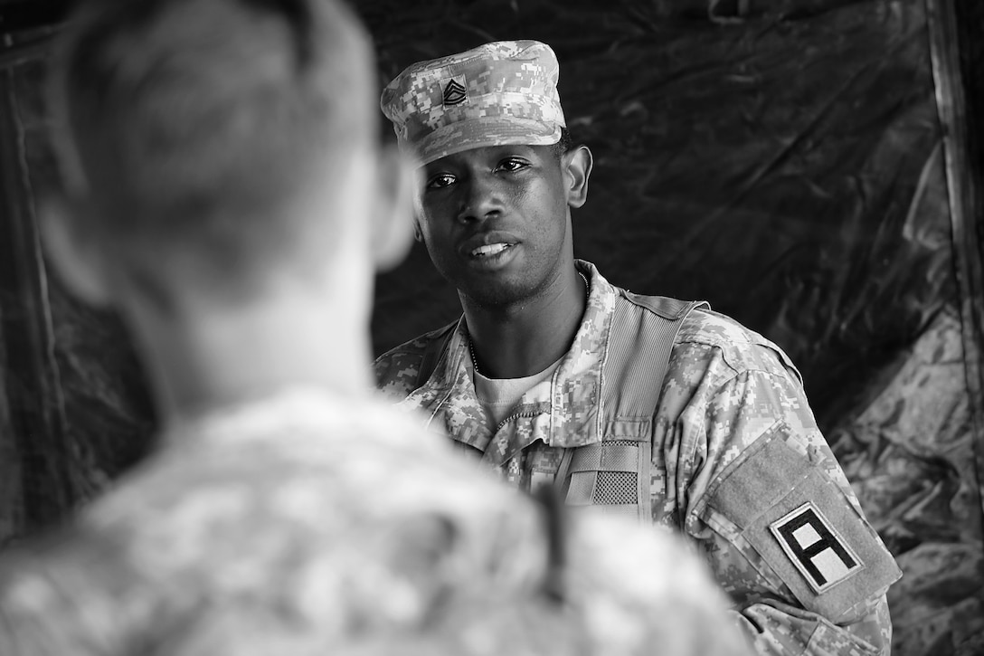 Sgt. 1st Class James McWilliams, observer-coach/trainer assigned to 1-409 Cavalry Battalion, 4th Cavalry Brigade, Fort Knox, speaks to a soldier assigned to the 371st Chemical Company, Greenwood, South Carolina, during a planning meeting at forward operating (training) base Justice, Fort McCoy, Wisconsin, July 11, 2016. (U.S. Army photo by Mr. Anthony L. Taylor/Released)