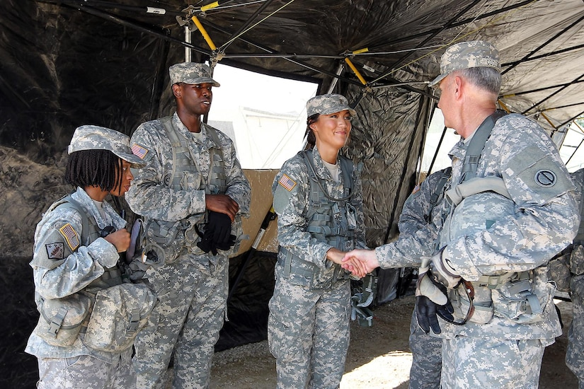 Col. Robert Cooley, right, deputy commander of the 85th Support Command, shakes hands with 2nd Lt. Stephanie Brooks, 1-383 training support battalion, 181st Infantry Brigade, during a meet with observer-coach/trainers at forward operating (training) base Justice, Fort McCoy, Wisconsin, July 11, 2016. (U.S. Army photo by Mr. Anthony L. Taylor/Released)