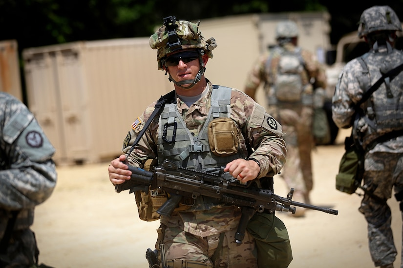 A soldier assigned to the 320th Military Police Company, Saint Petersburg, Florida, walks through tactical training base Patriot, Fort McCoy, Wisconsin, during Warrior Exercise 86-16-03, July 11, 2016. The soldiers assigned to TTB Patriot primarily train in convoy security, checkpoint procedures, and escort missions. (U.S. Army photo by Mr. Anthony L. Taylor/Released)
