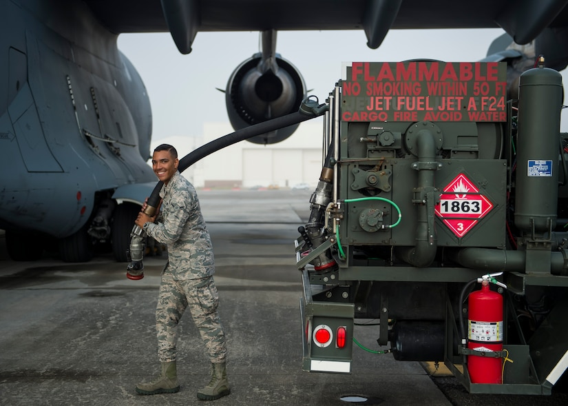 Airman Seth Roy, 628th Logistic Readiness Squadron fuels distribution operator, smiles while holding a fuel hose July 18, 2016, at Joint Base Charleston, S.C. Last year, over 50 Airmen of the 628th LRS fuels flight provided the base with more than 36 million gallons of fuel for missions throughout the base. (U.S. Air Force photo/Staff Sgt. Jared Trimarchi)