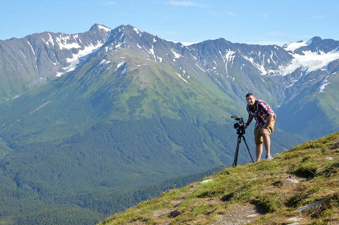 Tech. Sgt. Erik Gallion, a public affairs broadcaster assigned to the I.G. Brown Training and Education Center, pauses while filming lanscapes, July 12, 2016, in Alyeska Alaska. (U.S. Air National Guard photo by Master Sgt. Jerry D. Harlan)
