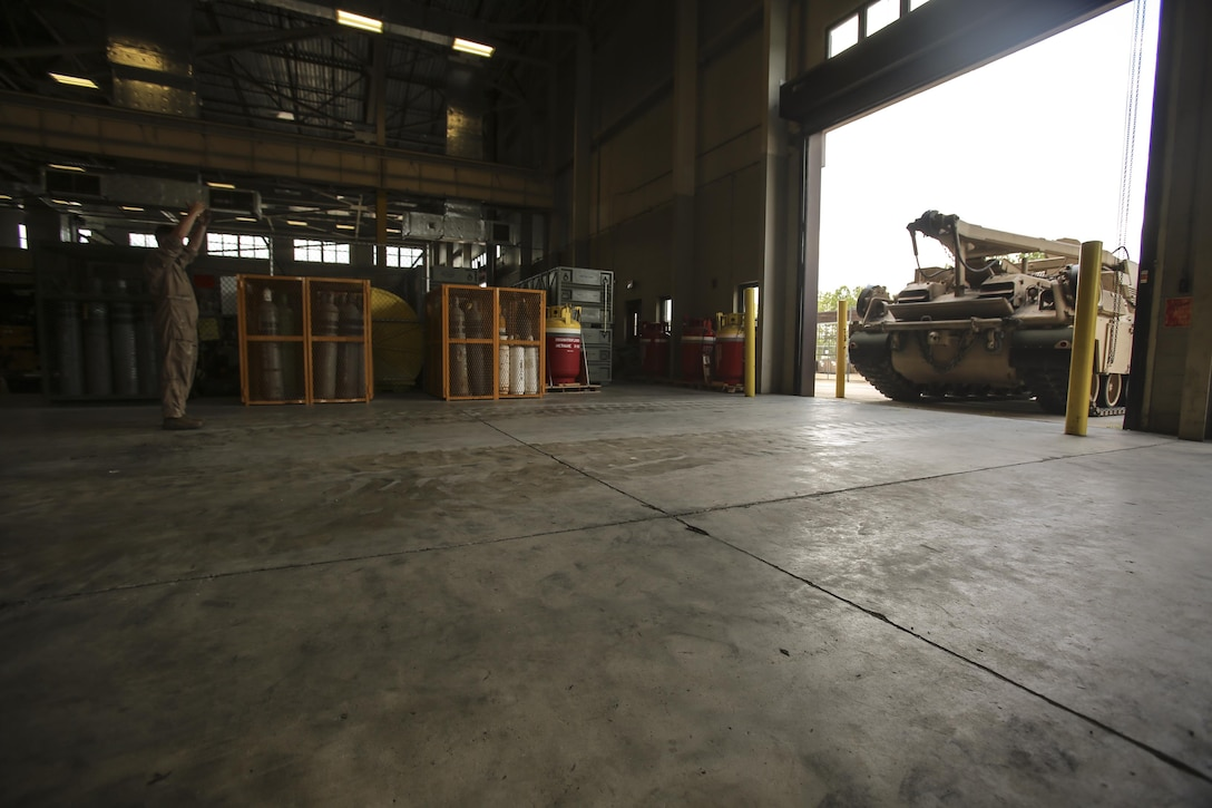A Marine with 2nd Maintenance Battalion helps ground guide an M88 Recovery Vehicle on to the floor to be repaired at Camp Lejeune, N.C., July 21, 2016. 2nd Maint. Bn. recently received the Chesty Puller Award, the Ground Safety Award and the Department of Defense Maintenance Award for the Marines excelling at their jobs individually and collectively. (U.S. Marine Corps photo by Lance Cpl. Miranda Faughn/Released)
