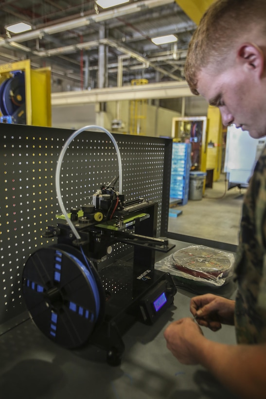 """Lance Cpl. Christopher Bigham, a metal worker with 2nd Maintenance Battalion works with a 3-D printer to discover new ways it can help the battalion at Camp Lejeune, N.C., July 21, 2016. """"If you can get caught up on your own work, you can work on what you want, but it's still your work so you're improving but being creative,"""" said Bigham, as to why he thinks the Marines excel at their jobs and why they have recently won various awards. (U.S. Marine Corps photo by Lance Cpl. Miranda Faughn/Released)"""