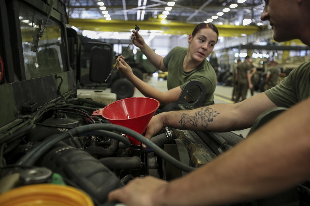 Two Marines with 2nd Maintenance Battalion work together to check the oil in a Humvee as part of a maintenance check at Camp Lejeune, N.C., July 21, 2016. 2nd Maint. Bn. was recently recognized for their abilities as a cohesive unit by earning the Chesty Puller Award, the Ground Safety Award and the Department of Defense Maintenance Award. (U.S. Marine Corps photo by Lance Cpl. Miranda Faughn/Released)