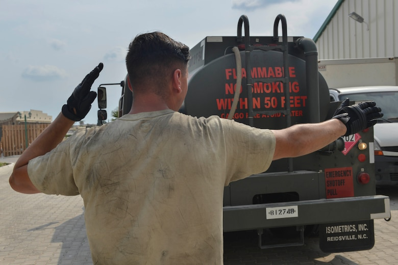 U.S. Air Force Airman 1st Class Trenton Beard, 39th Logistics Readiness Squadron (LRS) fuels specialist, guides Airman 1st Class Eduardo Reyes, 39th LRS fuels specialist, as he backs a fuel truck July 19, 2016, at Incirlik Air Base, Turkey. Beard and Reyes went around base refueling generators, enabling power to base facilities. (U.S. Air Force photo by Senior Airman John Nieves Camacho)