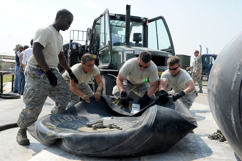 U.S. Air Force Staff Sgt. Brandon Jenkins, (left), Senior Airman Samantha Perez, Tech. Sgt. Tony Otis, and Staff Sgt. Christian Crider, 39th Logistics Readiness Squadron petroleum oils and lubricants flight Airmen, drag a fuel bladder to better allow fuel to flow while unloading into bulk storage July 22, 2016, at Incirlik Air Base, Turkey. Due to an extended loss of commercial power to the base, supplies, including food, water and fuel were delivered to sustain missions here at Incirlik. (U.S. Air Force photo by Staff Sgt. Jack Sanders)