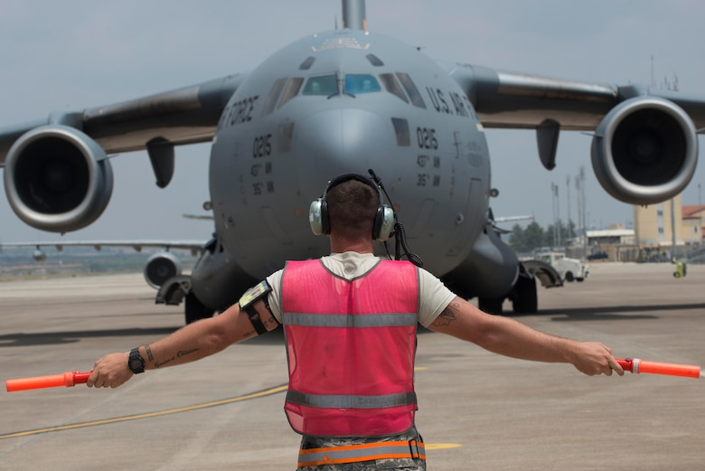 An Airman from the 728th Air Mobility Squadron marshals in a C-17 Globemaster III July 22, 2016, at Incirlik Air Base Turkey. The C-17 carried fuel bladders that were distributed for operations at Incirlik Air Base. (U.S. Air Force photo by Senior Airman John Nieves Camacho)