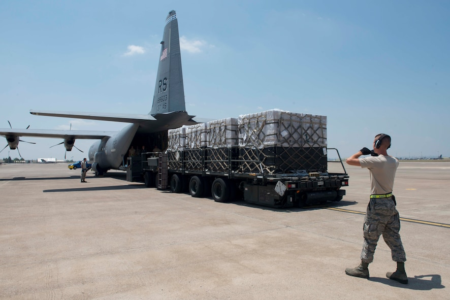 An Airman from the 728th Air Mobility Squadron guides a truck back July 22, 2016, at Incirlik Air Base Turkey. The truck contained cargo received from a C-130J Super Hercules aircraft. (U.S. Air Force photo by Senior Airman John Nieves Camacho)