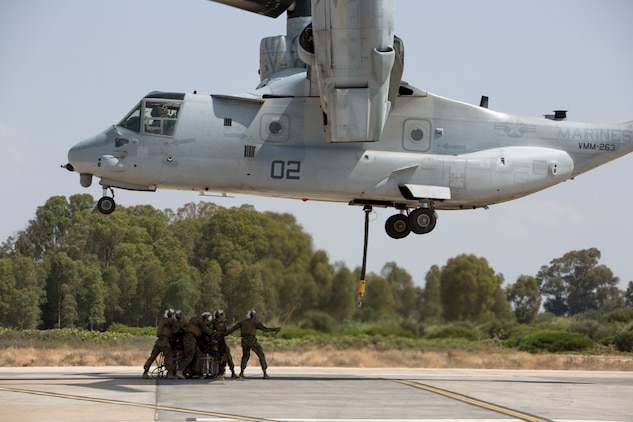 Landing support specialists with Combat Logistics Battalion 2, Special Purpose Marine Air-Ground Task Force-Crisis Response-Africa, prepare to attach a 1,098 pound pallet of Meals, Ready to Eat to an MV-22B Osprey during a helicopter support team exercise aboard Naval Station Rota, Spain, July 6, 2016. External lift training prepares the Marines to efficiently attach cargo to the aircraft and helps qualify air crew in the mission-essential task of rapid insertion and extraction in a possible crisis response scenario. (U.S. Marine Corps photo by Staff Sgt. Tia Nagle/Released)