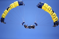 "Sailors Brandon Peterson and TJ Amdahl perform the parabatic maneuver known as ""bringing up a down plane"" during Cheyenne Frontier Days in Cheyenne, Wyo., July 25, 2016. The sailors are members of the Leap Frogs, the Navy's parachute team, which received air support from Wyoming Air National Guard C-130 Hercules aircraft and crews during for event. Army National Guard photo by Sgt. 1st Class Jimmy McGuire"