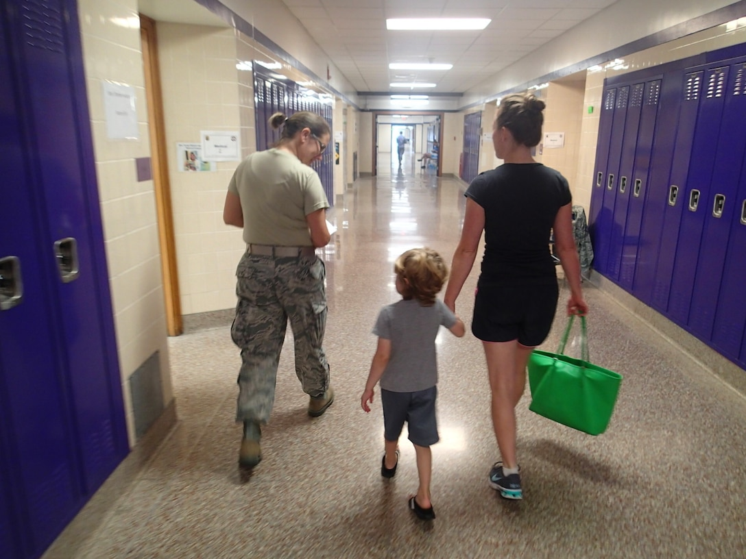 """Tech Sgt. Lora """"Lori"""" Olsen, a medical technician with the 174th Medical Group out of Syracuse, N.Y., leads a patient and her son from being seen by a medical provider to their next stop in optometry during Greater Chenango Cares, July 24, 2016.  Greater Chenango Cares is one of the Innovative Readiness Training events which provides real-world training in a joint civil-military environment while delivering world-class medical care to the people of Chenango County, N.Y., from July 15-24."""