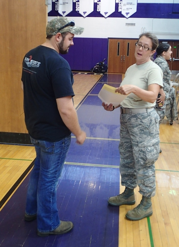 """Tech Sgt. Lora """"Lori"""" Olsen, a medical technician with the 174th Medical Group out of Syracuse, N.Y., checks a patient's information before leading them to the medical section for care during Greater Chenango Cares, July 23, 2016.  Greater Chenango Cares is one of the Innovative Readiness Training events which provides real-world training in a joint civil-military environment while delivering world-class medical care to the people of Chenango County, N.Y., from July 15-24."""