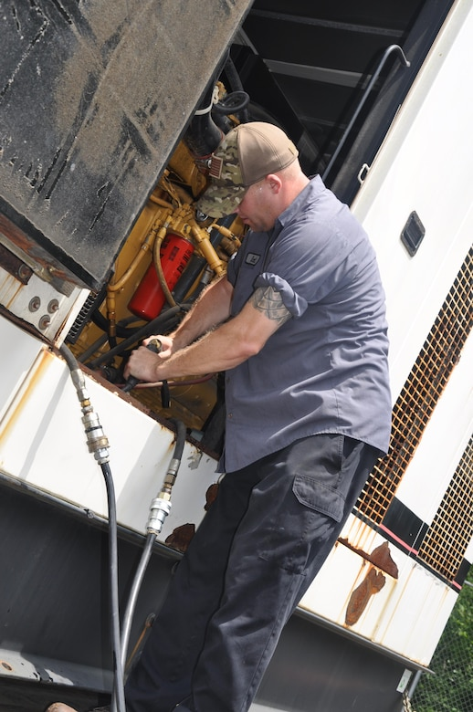 A member of the Federal Emergency Management Agency's Emergency Support Function simulates installation of a generator during a regional power mission exercise conducted July 20 at the FEMA Distribution Center in Atlanta, Georgia.